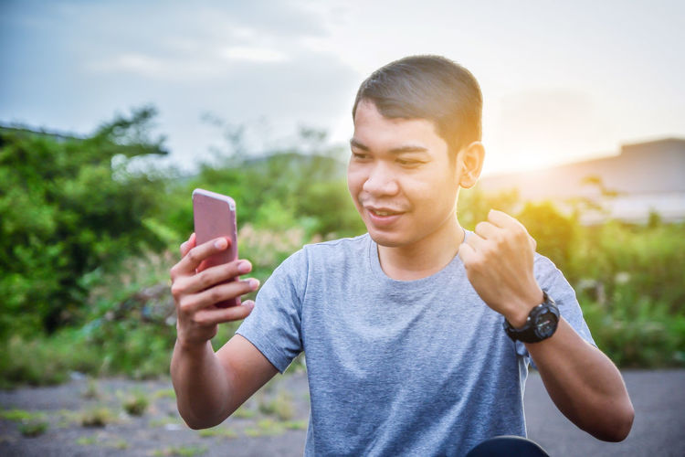 Man clenching fist while using mobile phone against sky