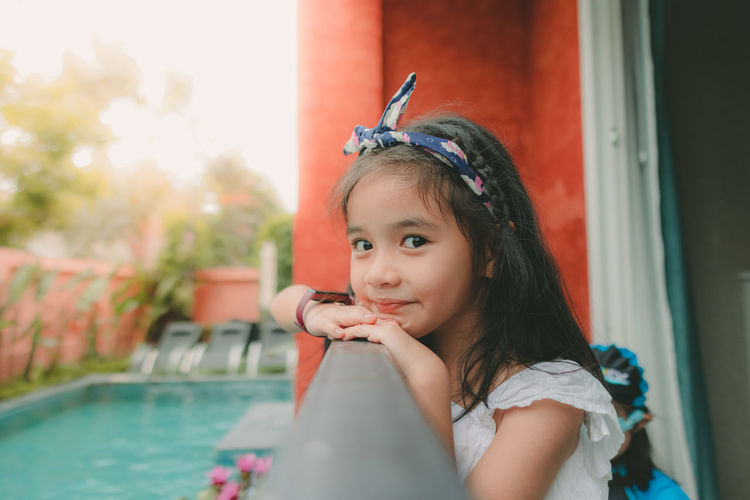 Portrait of cute girl looking at swimming pool