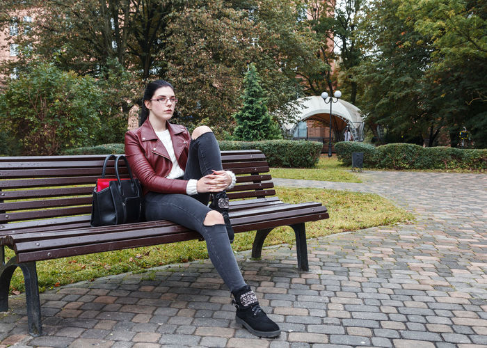 Portrait of man sitting on bench in park