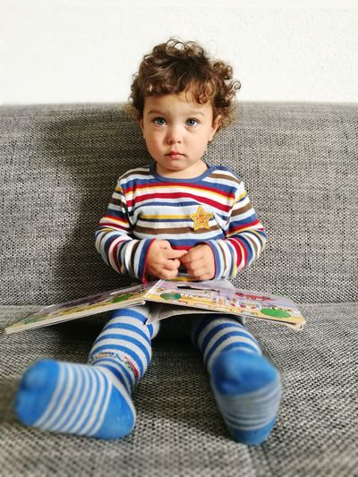 Portrait Of Cute Boy Sitting On Sofa