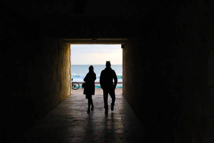Silhouette Man And Woman Walking In Tunnel