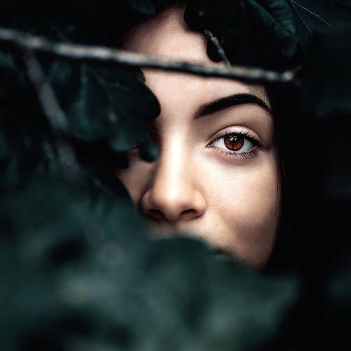 Close-up portrait of young woman amidst plants