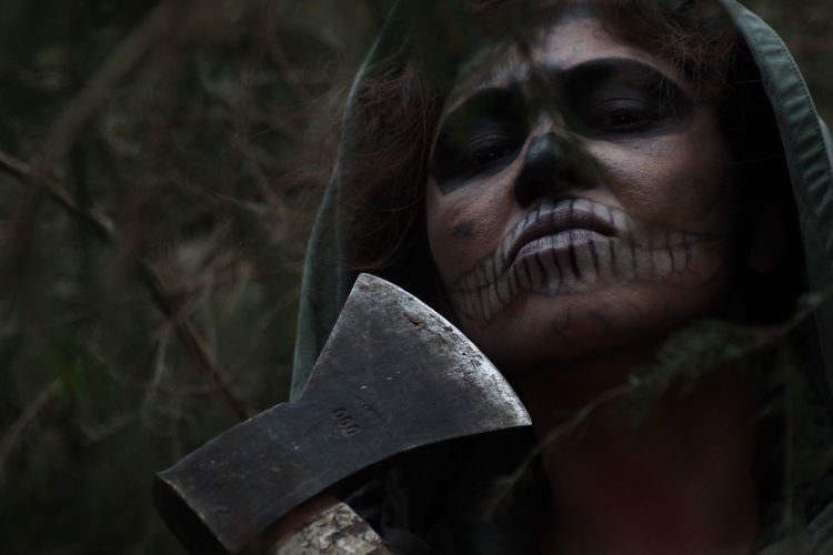 Portrait of woman with face paint holding axe at forest