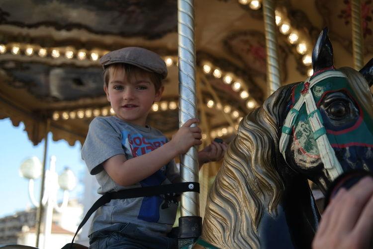 Portrait of a boy enjoying merry-go-round ride