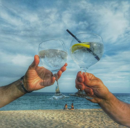 Cropped Image Of Friends Toasting Drink At Beach Against Sky