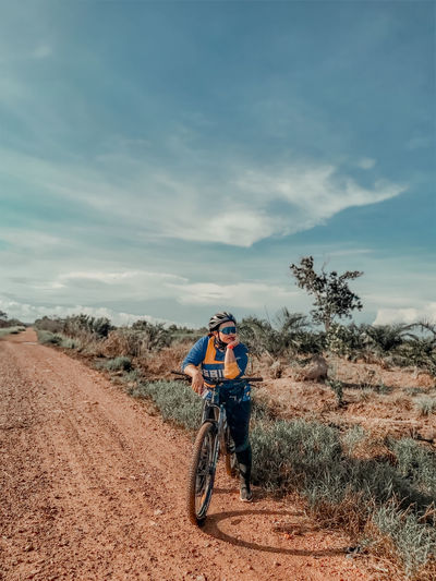 Full length of woman standing with bicycle on dirt road against sky