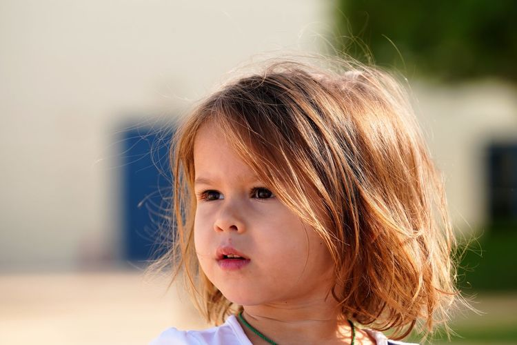 Close-up of cute girl looking away while standing outdoors