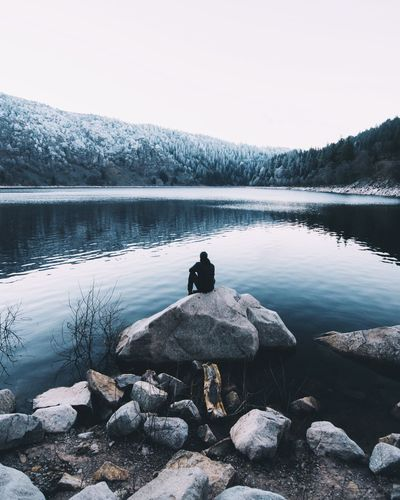 Man relaxing by lake against sky