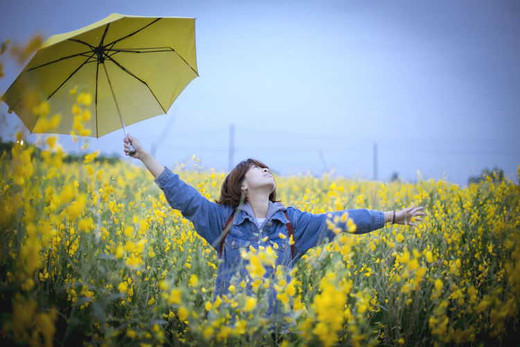 Young woman with yellow flowers in field