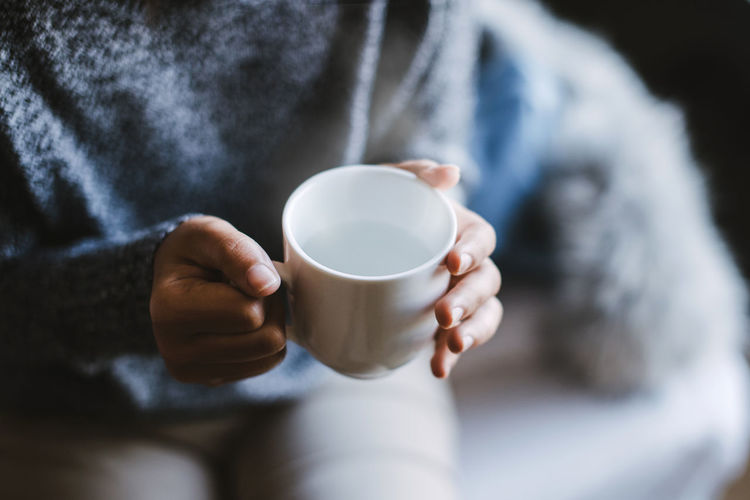 Close-up of a woman's hand holding a cup of hot water, vintage tone. Drink Cup Mug Coffee - Drink Coffee Cup Coffee Refreshment Food And Drink Holding One Person Midsection Drinking Adult Close-up Human Hand Casual Clothing Human Body Part Hand Hot Drink Crockery Latte Winter Cool Hot
