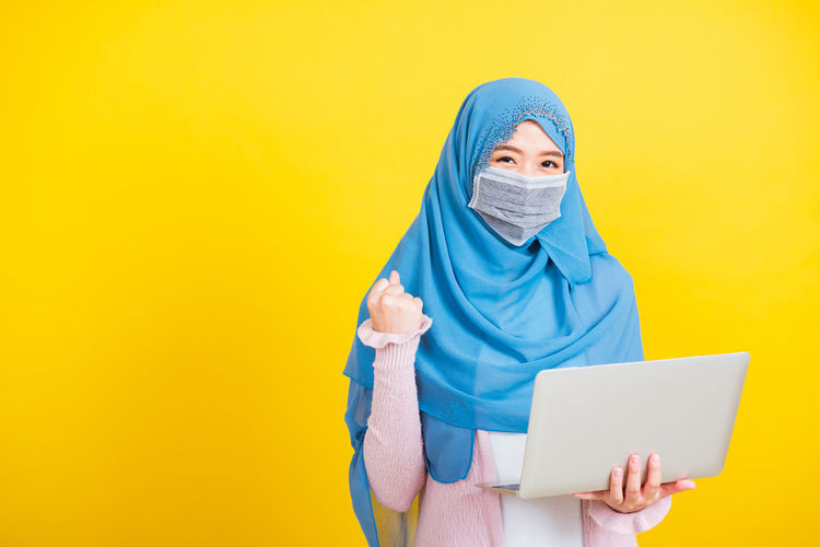 Young woman wearing mask holding laptop standing against yellow background