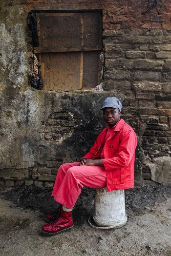 Portrait of man sitting against brick wall
