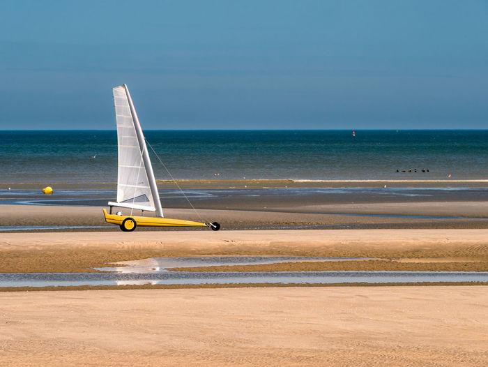 Sailboat on beach against sky