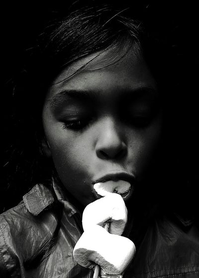 Close-up of girl eating marshmallow in dark
