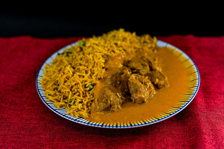 Close-Up Rice And Curry Served In Plate On Table Against Black Background
