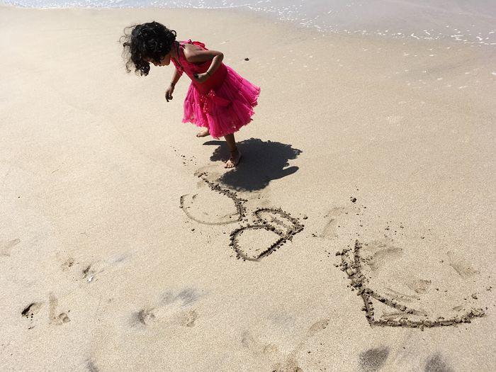 High angle view of girl writing on sand at beach