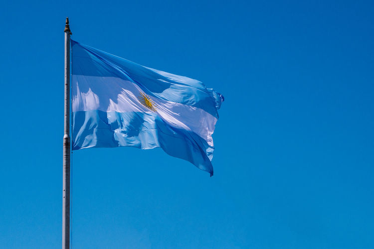 Low angle view of argentinian flag waving against clear blue sky