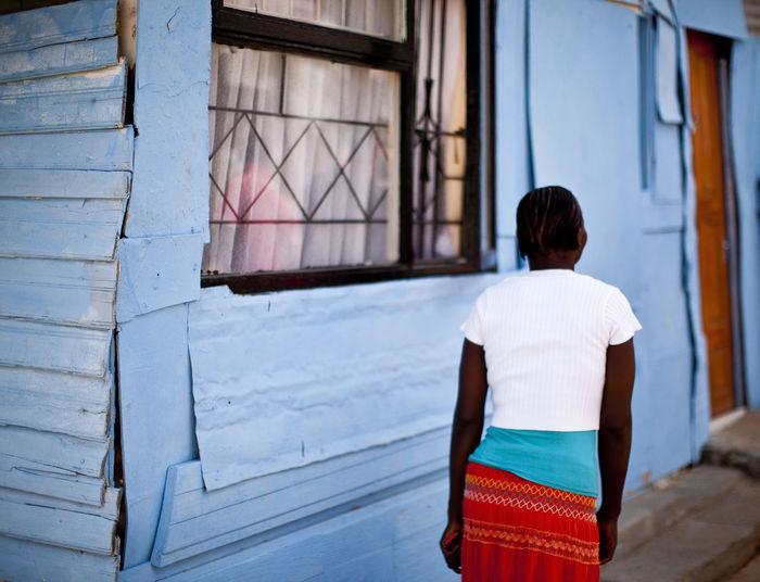 Rear view of woman walking by house in village