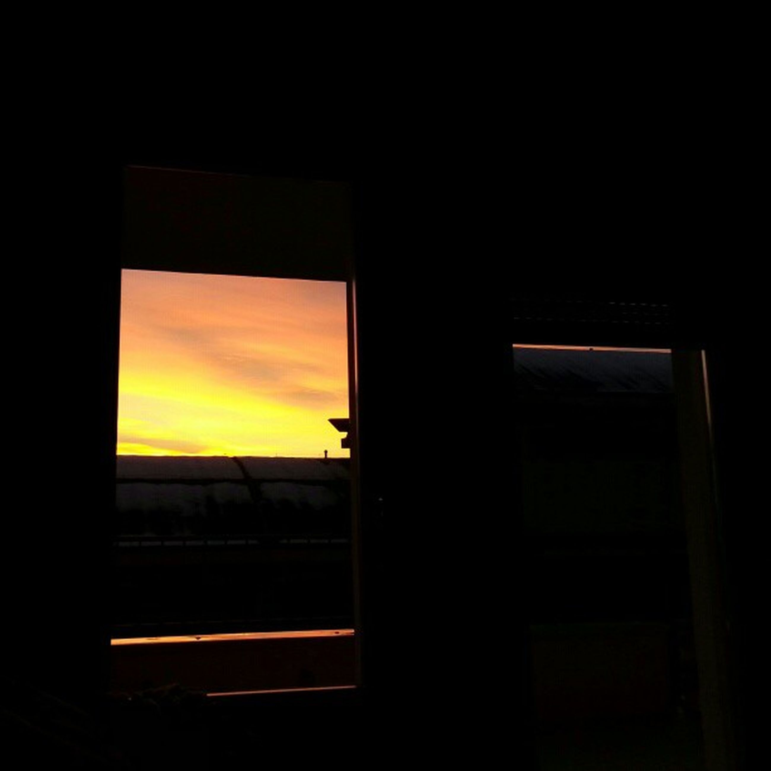 window, indoors, sunset, glass - material, transportation, transparent, sky, silhouette, vehicle interior, dark, mode of transport, looking through window, built structure, architecture, cloud - sky, orange color, car, no people, land vehicle, airplane