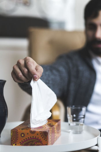 Midsection of man holding drink in restaurant