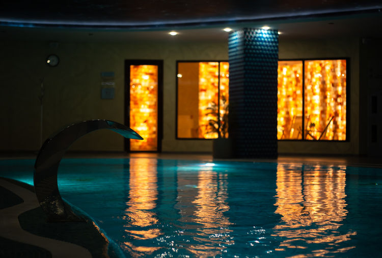 Reflection of illuminated window in swimming pool