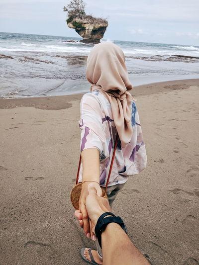 Boyfriend holding hand of girlfriend at beach