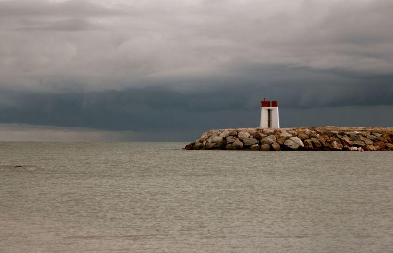 Lighthouse on beach against cloudy sky