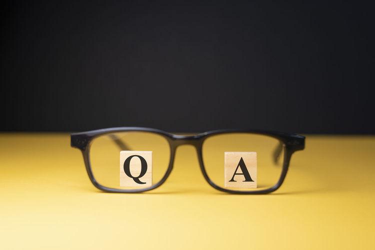 Close-up of yellow eyeglasses against black background