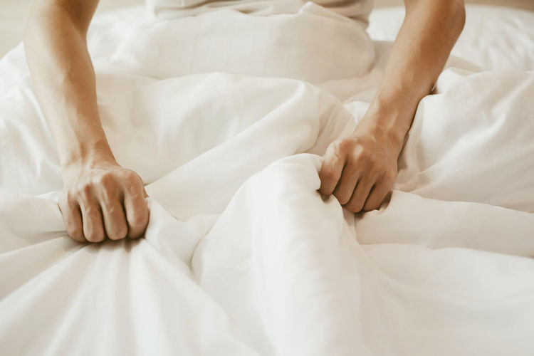 Low section of person lying on bed