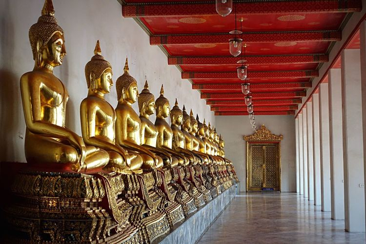 Gold buddha statues in row at wat pho corridor