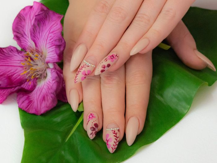 Cropped hands of woman with pink nail polish on leaf