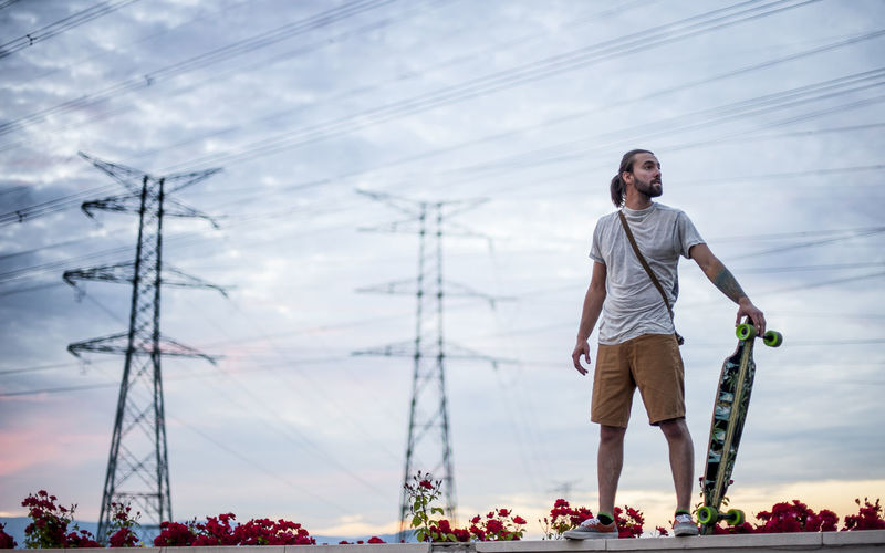 Man looking away while standing against sky