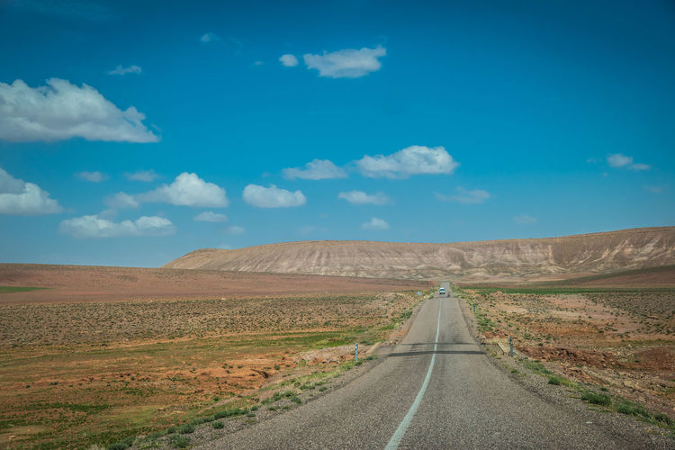 Empty road amidst land against sky