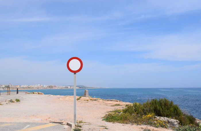 Sea and a sign Sign Sky Communication Road Sign Sea Guidance Water Land No People Horizon Over Water Day Information Scenics - Nature Road Nature Information Sign Horizon Beach Tranquility Beauty In Nature Outdoors Stop Sign Mediterranean  No Go Circle