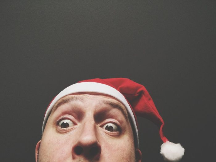 Cropped image of surprised man wearing santa hat against black background