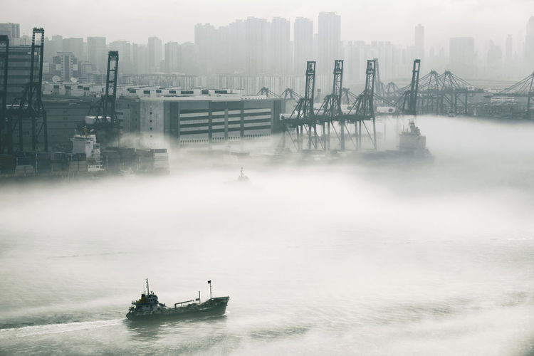 Urban Skyline Skyscraper Fog Environment Social Issues Business Finance And Industry Silhouette Building Exterior Cityscape City Downtown District Extreme Weather Nautical Vessel Smog Water Architecture Built Structure Backgrounds Outdoors Awe