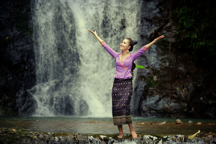 Woman With Arms Raised Against River