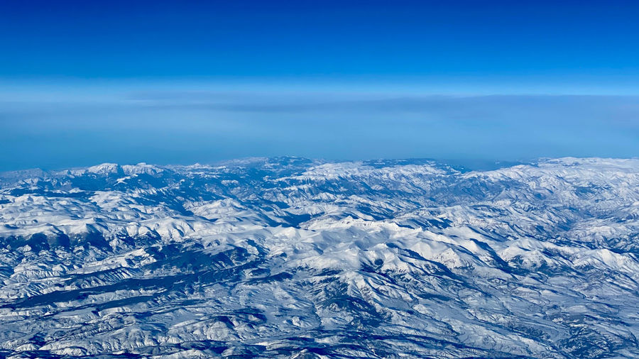 Ariel view of snowcapped mountains against blue sky