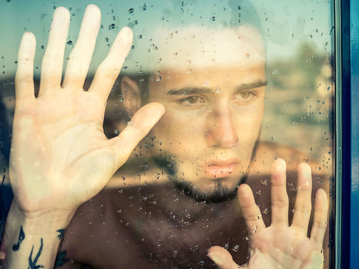 Close-up portrait of man looking through wet glass window