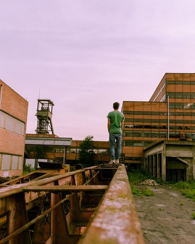Rear view of young man standing at construction site against sky