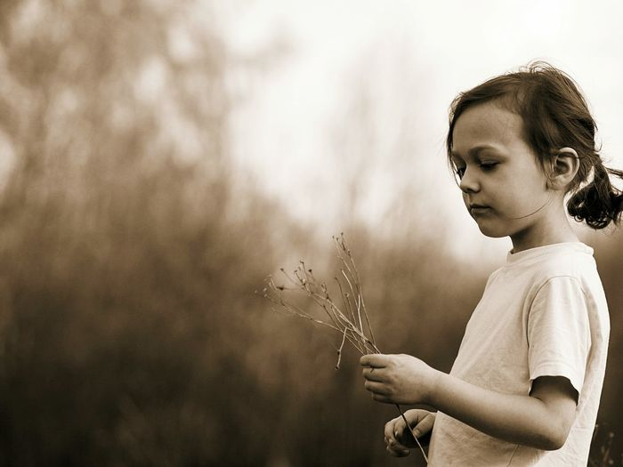 Side view of girl holding dead plant while standing outdoors
