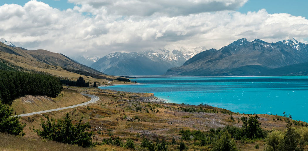 Scenic view of turquoise lake pukaki and mountains against dramatic sky