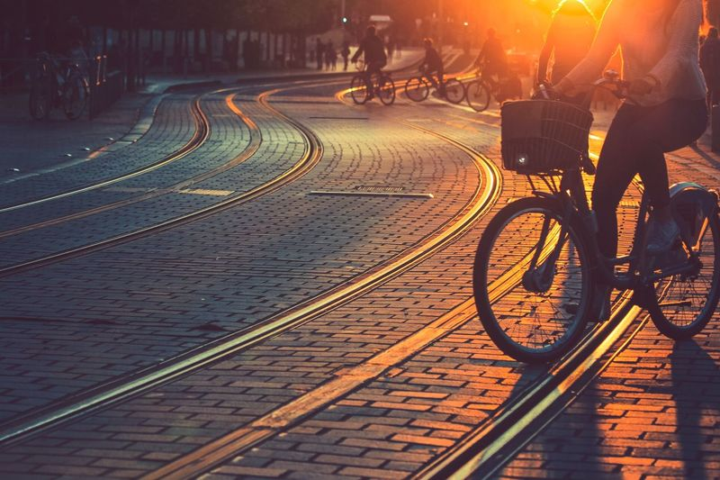 Low Section Of Woman Riding Bicycle On Tramway During Sunset