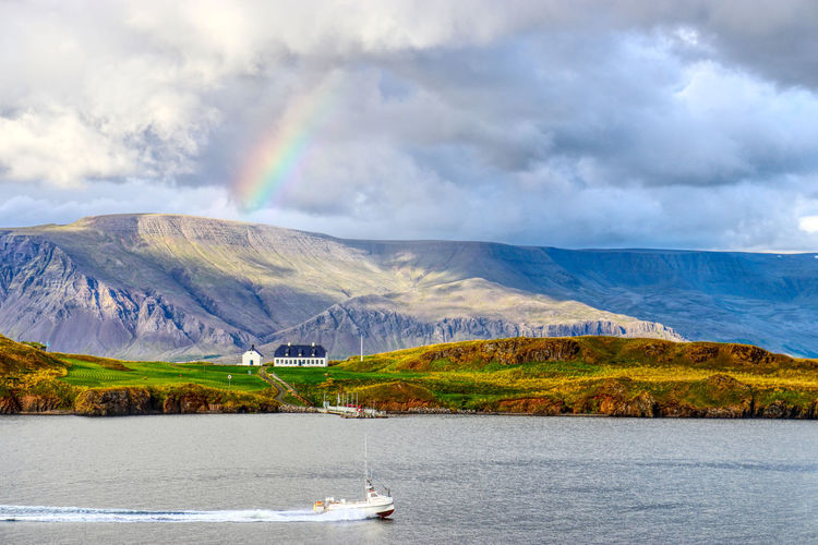 Scenic View Of Rainbow Over Lake And Mountains Against Sky