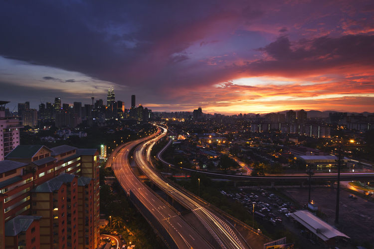 Main road leading into the city is illuminated during the sunset. Architecture Building Exterior Built Structure City City Life Cityscape Cloud - Sky High Angle View High Street Illuminated Light Trail Long Exposure Modern Motion Night No People Outdoors Road Sky Skyscraper Speed Traffic Transportation Travel Destinations Urban Skyline The Architect - 2017 EyeEm Awards