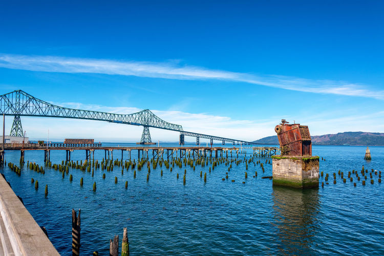 Ruins of an old historic pier with the Astoria Megler Bridge in the background connected Oregon to Washington at the mouth of the Columbia River Astoria Oregon Columbia River Travel Travel Destinations Tourism Outdoors Day Nature No People USA Pacific Northwest  Pier Dock Astoria-megler Bridge Astoria Oregon Astoria Megler Bridge Bridge Bridge - Man Made Structure Water Built Structure Sky Architecture Connection Transportation Sea Blue Cloud - Sky Waterfront Beauty In Nature Building Exterior Bay Wooden Post