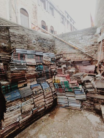 Stack of books on staircase by buildings in city