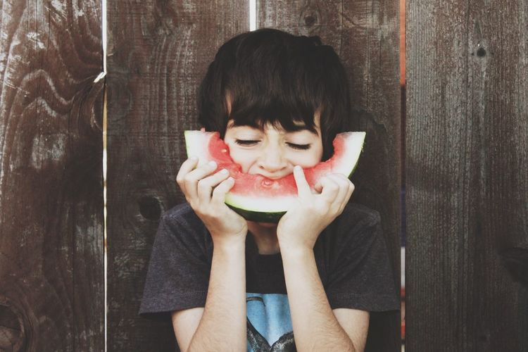 Boy Eating Watermelon Against Wooden Fence
