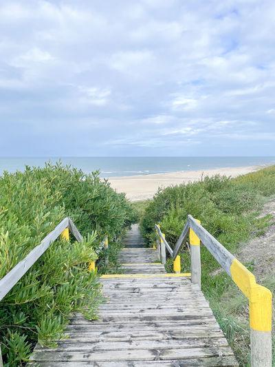 Boardwalk leading towards sea against sky