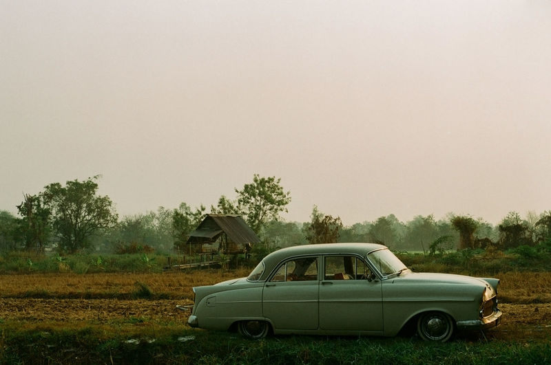 Vintage car staying at a country house. Mode Of Transportation Car Motor Vehicle Land Vehicle Transportation Tree Field Plant Nature Sky Copy Space Day Land Clear Sky Landscape No People Retro Styled Stationary Outdoors Old Vintage Vintage Car Classic Car